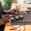Senior african electrician using soldering iron — Stock Photo