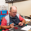 Senior man working in workshop - Stock Photo