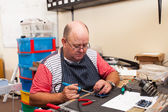 Senior man working in workshop — Stock Photo