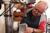 Senior metal worker using industrial drilling machine — Stock Photo