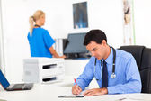 Doctor writing medical report — Stock Photo