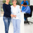 Beautiful daughter taking her elderly mother to doctor — Stock Photo