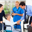 Friendly medical doctor greeting senior patient — Stock Photo