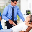 Male doctor greeting senior patient before checkup - Stock Photo