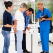 Foto Stock: Male doctor measuring patient's height and weight on scale