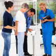 Male doctor measuring patient's height and weight on scale — ストック写真