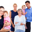Stock Photo: Young woman holding her baby with extended family on background
