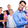 Stockfoto: Father holding his daughter with extended family on background