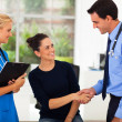 Doctor congratulating female patient for her successful recovery — Stock Photo
