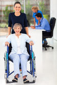 Young woman and senior mother in doctor's office — Stock Photo