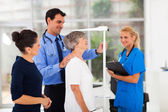 General practitioner measuring senior patient's height — Stockfoto