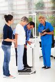 мужской доктор измерения высоты и веса по шкале пациента — Стоковое фото