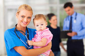 Female nurse holding baby girl — Stock Photo