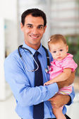 Pediatric doctor holding baby girl — Stock Photo
