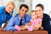 Woman and baby girl with health workers — Stock Photo