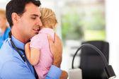 Pédiatre attentionné étreignant un bébé malade — Photo