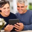 Middle aged couple reading emails — Stok Fotoğraf #25036559
