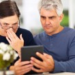 Middle aged couple reading shocking news — Stock Photo #25036847