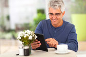Middle aged man surfing the internet using tablet computer — Foto Stock