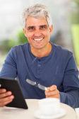 šťastný střední letitý muž s tabletovým počítačem — Stock fotografie