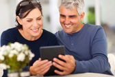 Middle aged couple reading emails — Stok fotoğraf