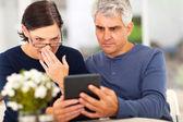 Middle aged couple reading shocking news — Stock Photo
