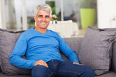Middle aged man relaxing on sofa — Stock Photo