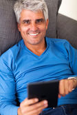Mature man using tablet computer — Stock Photo