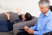 Middle aged therapist consulting patient — Stock Photo