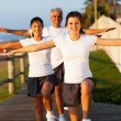 Modern active family exercising at the beach — Stock Photo