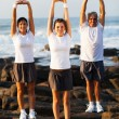 Family exercising at the beach - Stock Photo