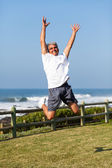 Senior man jumping at the beach — Stock Photo