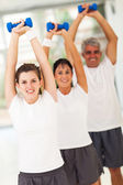 Line up of family lifting dumbbells — Stock Photo
