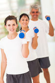 Line up of family exercising with dumbbells — Stock Photo