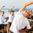 Mid age man exercising at the beach - Stock Photo