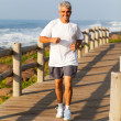 Active middle aged man jogging at the beach — Stock Photo