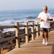Fit senior man running at the beach — Stock Photo