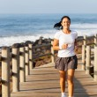 Fit mid age woman jogging at the beach — Stock Photo
