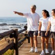 Healthy family walking on beach - Stock Photo