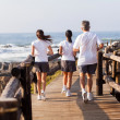 Rear view of family jogging on beach — Stock Photo