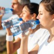 Active family drinking water after jogging — Stock Photo