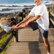 Active mature man stretching leg at the beach — Stock Photo #25267797