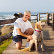 Active senior man and his dog at the beach — Stock Photo