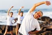 Mitten av ålder man tränar på stranden — Stockfoto