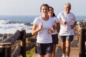 Healthy family jogging on beach — Stock Photo