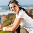 Beautiful teen girl with water bottle after exercise - Stock Photo