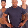 Muscular man with two women posing — Foto de Stock