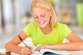 Happy preteen girl writing homework — Zdjęcie stockowe