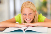 Happy teen girl lying on book — Stock Photo