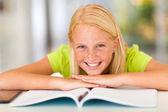 Happy teen girl lying on book — Stock Photo